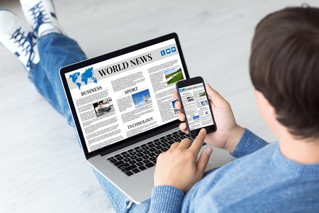 Man holding computer and phone with app world news in screen
