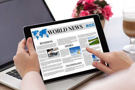 woman hands holding tablet computer with app world news screen and laptop