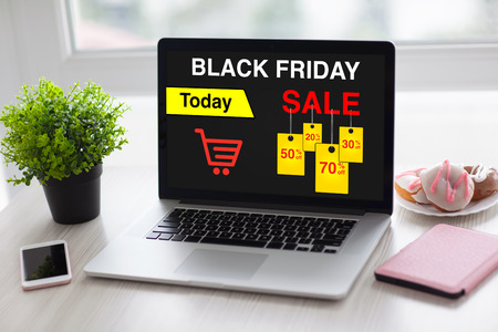 laptop with sale black friday on screen and phone in the office