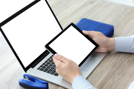 male hands holding tablet and laptop with isolated screen in office