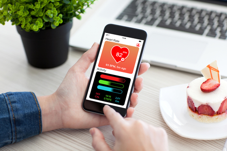 Women hands holding phone with app health tracking activity on screen
