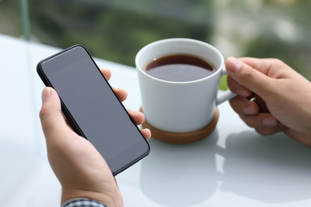 men hands holding phone with black screen and cup of tea in summer cafe