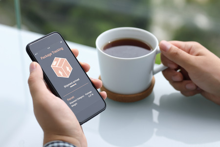 men hands holding phone with app tracking delivery package screen and cup of tea in summer cafe Фото со стока