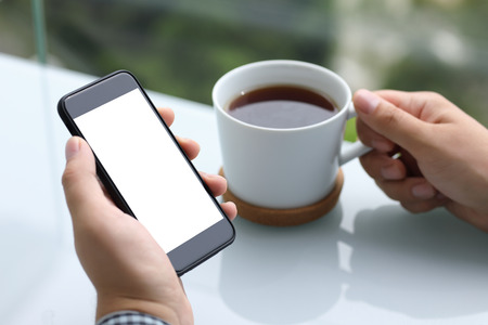 men hands holding phone with isolated screen and cup of tea in summer cafe