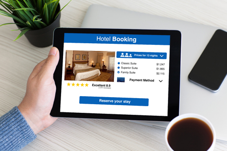 man hand holding computer tablet with app hotel booking on screen over table in office