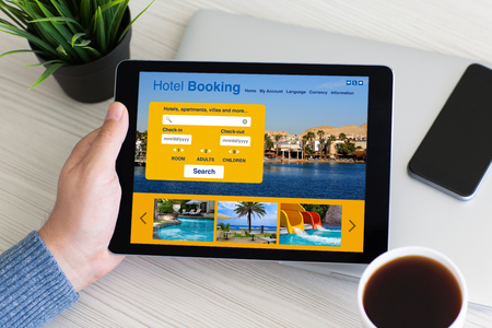man hand holding computer tablet with app hotel booking on screen in office