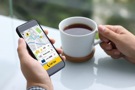 men hands holding phone with app call taxi on screen and cup of tea in summer cafe Фото со стока
