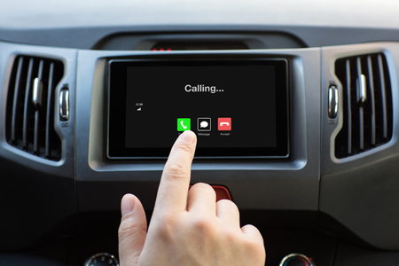male hand touching multimedia system with phone calling on screen in car Фото со стока