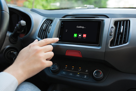Man hand touching multimedia system with phone calling on screen in car