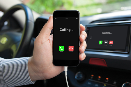 man hand holding Phone and multimedia system with calling on screen in car