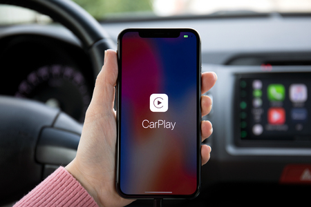 Alushta, Russia - December 16, 2017: Woman hand holding iPhone X with CarPlay on the screen in the car. iPhone 10 was created and developed by the Apple inc.