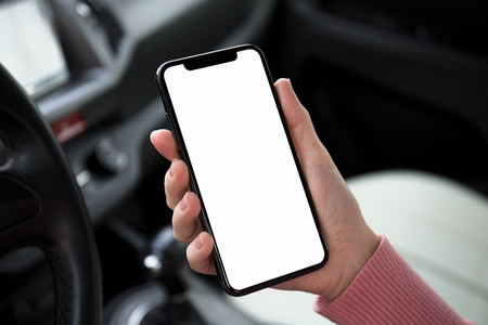women hand holding phone with isolated screen in the car Фото со стока