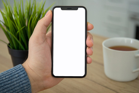 Male hand holding black touch phone with isolated screen in room