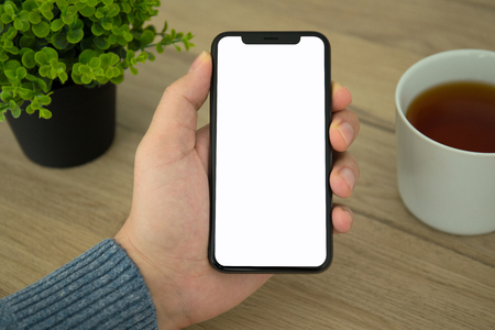 Male hand holding black touch phone with isolated screen above the table