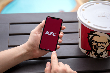 Koh Samui, Thailand - January 19, 2018: Man hands holding iPhone X with app Kentucky Fried Chicken. KFC is an American fast food restaurant chain that specializes in fried chicken.