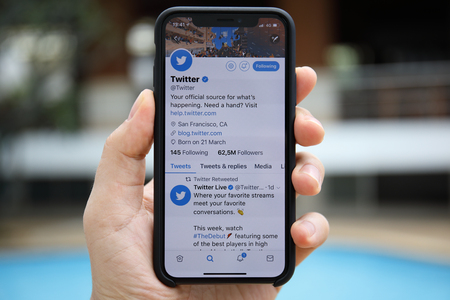 Koh Samui, Thailand - January 22, 2018: Man hand holding iPhone X with social networking service Twitter on the screen. iPhone 10 was created and developed by the Apple inc. Редакционное