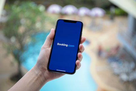 Koh Samui, Thailand - January 31, 2018: Woman hand holding iPhone X with application Booking.com online hotel reservations on the screen. iPhone 10 was created and developed by the Apple inc. Редакционное