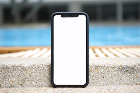 touch phone with isolated screen on background of the pool Фото со стока