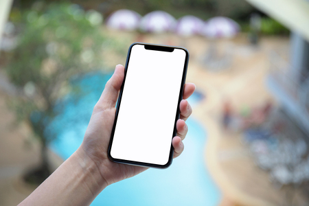 female hand holding phone with an isolated screen on background of the pool in hotel Stock Photo