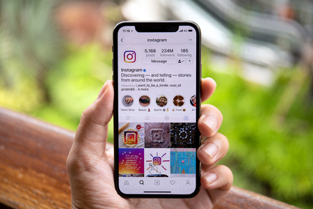 Koh Samui, Thailand - April 9, 2018: Man hand holding iPhone X with social networking service Instagram on the screen. iPhone 10 was created and developed by the Apple inc. Редакционное