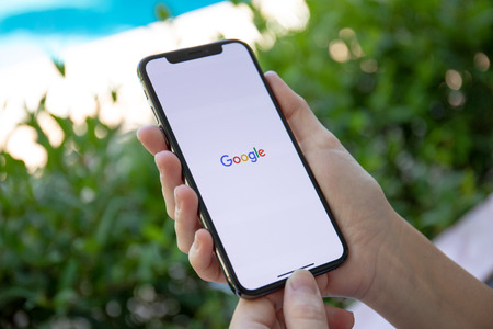 Koh Samui, Thailand - March 21, 2018: Woman holding iPhone X with social networking service Google on the screen. iPhone was created and developed by the Apple inc.