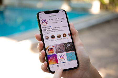 Koh Samui, Thailand - March 21, 2018: Woman hand holding iPhone X with social networking service Instagram on the screen. iPhone 10 was created and developed by the Apple inc.