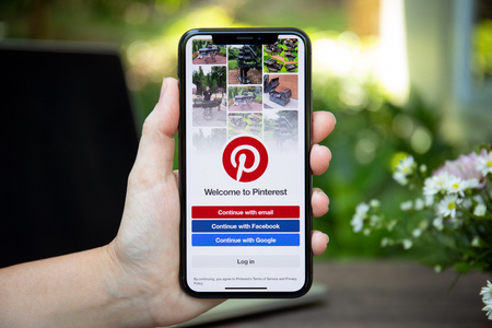Koh Samui, Thailand - March 23, 2018: Woman hand holding iPhone X with social Internet service Pinterest on the screen. iPhone 10 was created and developed by the Apple inc. Editorial