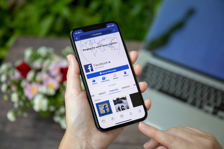 Koh Samui, Thailand - March 23, 2018: Woman holding iPhone X with social networking service Facebook on the screen. iPhone 10 was created and developed by the Apple inc. Редакционное