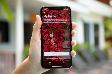 Koh Samui, Thailand - March 30, 2018: Woman hand holding iPhone X with app Home in the screen. iPhone 10 was created and developed by the Apple inc. Редакционное