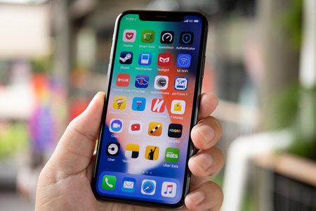 Koh Samui, Thailand - 9. April 2018: Mannhand, die iPhone X mit IOS 11 auf dem Bildschirm hält. Das iPhone 10 wurde von Apple Inc. erstellt und entwickelt.