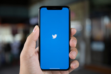 Koh Samui, Thailand - April 15, 2018: Man hand holding iPhone X with social networking service Twitter on the screen. iPhone 10 was created and developed by the Apple inc. Редакционное