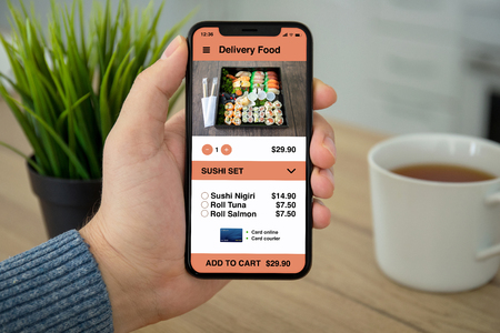 male hand holding phone with app for deliveriy sushi food on the screen