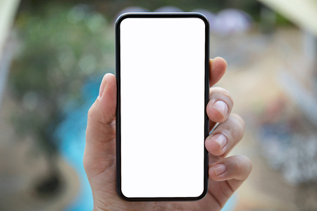 man hand holding phone with isolated screen on the background of the pool Фото со стока
