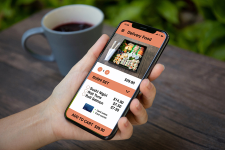 female hand holding phone with app for delivery sushi food on the screen