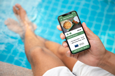 man holding phone with app delivery sushi food on screen by the pool