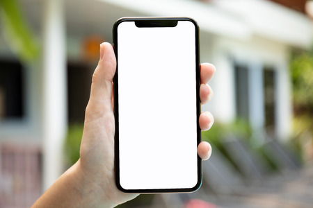 female hand holding phone with isolated screen on background of the house