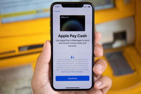Koh Samui, Tailandia - 25 de marzo de 2018: Mano de hombre sosteniendo el iPhone X con Apple Pay en la pantalla. El iPhone 10 fue creado y desarrollado por Apple inc.