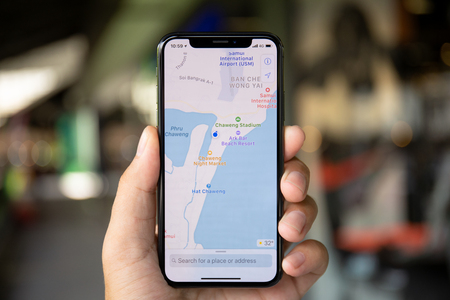 Koh Samui, Thailand - April 15, 2018: Man hands holding iPhone X with application cartographical service Apple Maps in the screen. iPhone 10 was created and developed by the Apple inc. Редакционное
