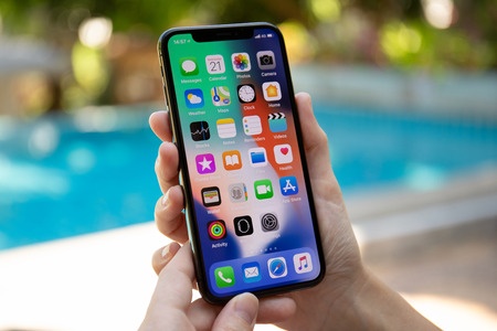 Koh Samui, Thailand - March 21, 2018: Woman hand holding iPhone X with IOS 11 on the screen. iPhone 10 was created and developed by the Apple inc.