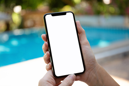 female hands holding phone with isolated screen on background of the pool Stock Photo