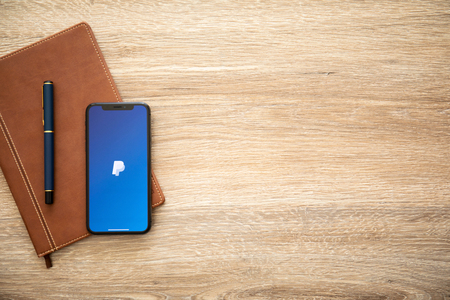 Alushta, Russia - August 22, 2018: iPhone X with service PayPal on the screen and background wooden desk. iPhone 10 was created and developed by the Apple inc.