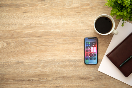 Alushta, Russia - August 26, 2018: iPhone X with home screen Control Center and background wooden desk. iPhone 10 was created and developed by the Apple inc.