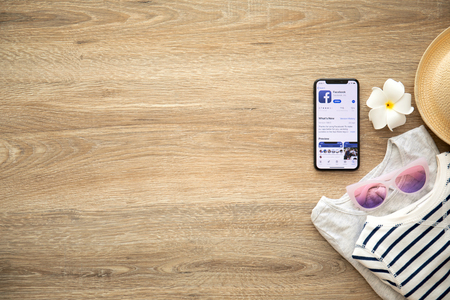 Alushta, Russia - August 26, 2018: iPhone X with social networking service Facebook on the screen and background wooden desk. iPhone 10 was created and developed by the Apple inc.