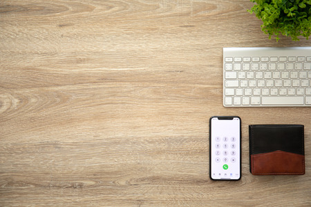 Alushta, Russia - August 26, 2018: iPhone X with call number on the screen and background wooden desk. iPhone 10 was created and developed by the Apple inc.