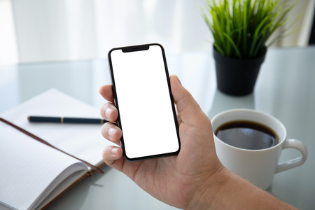 man hand holding phone with isolated screen over table in the office Фото со стока