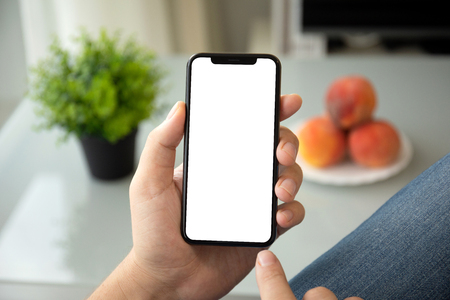 man hands holding phone with isolated screen in room of the house