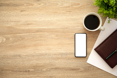 phone with isolated screen on wooden table near notebook and cup of coffee