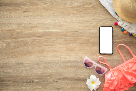 phone with isolated screen on wooden table near clothes and things for holidays Фото со стока