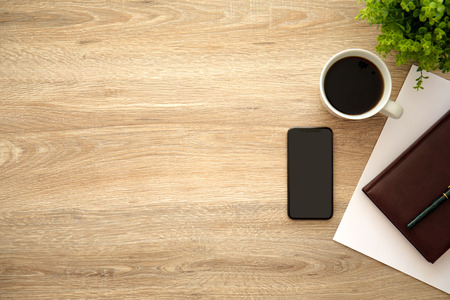 phone with black screen on wooden table near notebook and cup of coffee