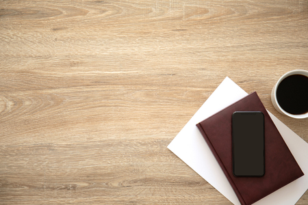phone with an black screen on wooden table near notebook and cup of coffee Фото со стока